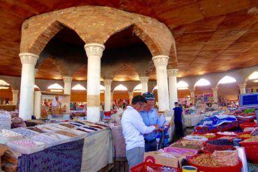 Penjikent Bazaar with two men looking at goods, tajikistan shopping