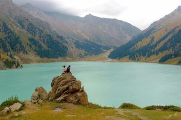 Girls sitting next to the Big Almaty Lake Kazakhstan travel