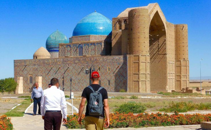 tourist and guide walking towards Yassawi mausoleum, kazakhstan travel