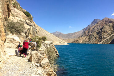 people walking on narrow mountain path in Tajikistan