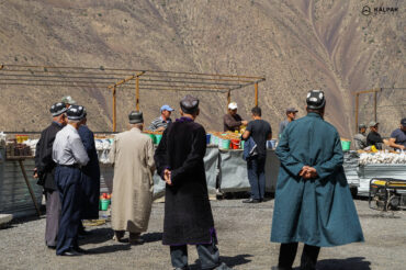 Tajik men in traditional clothes in market in the mountains