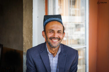 Tajik man smiling in traditional skullcap