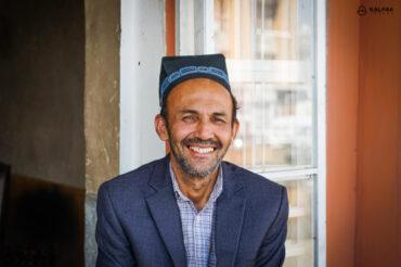 Tajik man smiling in traditional skullcap