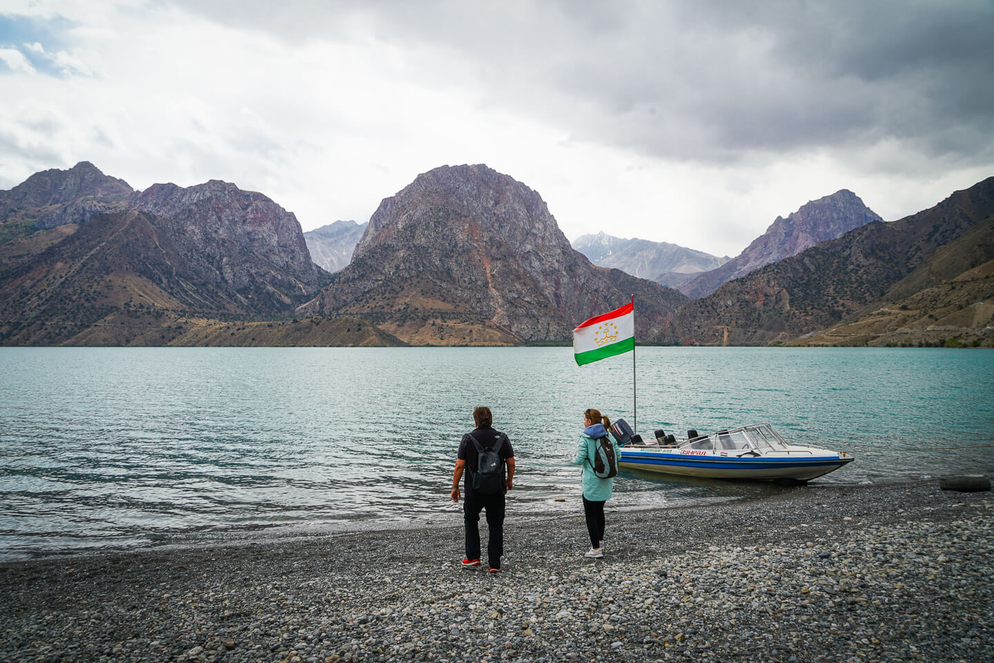 Iskanderkul lake shore with 2 travelers near the boat