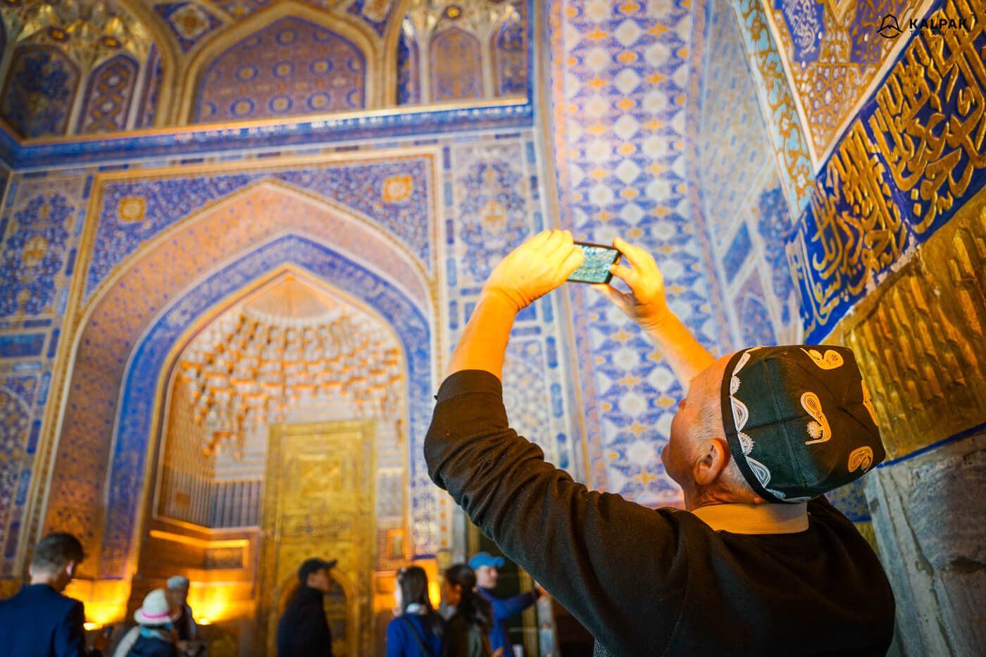 Golden building of Registan, men taking picture in national Uzbek hat
